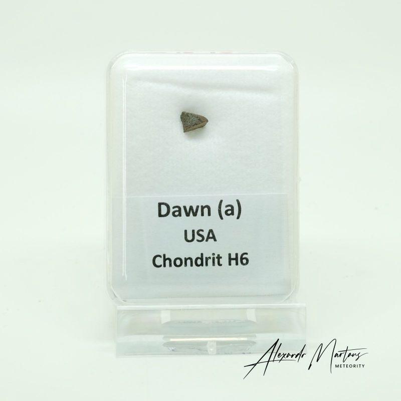 Kamenný meteorit z lokality Dawn (a) o váze 0,12 gramů E-meteority